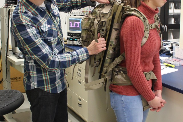 Dan Milliken, CERDEC CP&ID engineer, inspects the Energy Harvester Assault Pack, or EHAP, worn by Julie Douglas, CERDEC CP&ID engineer. The EHAP captures the energy expended by a Soldier's natural movements and converts it into useable energy, allowing for extended missions in the field.