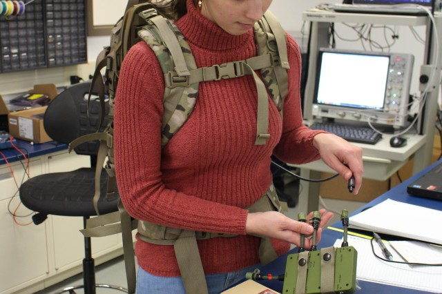 """Julie Douglas, CERDEC CP&ID engineer, demonstrates how the Integrated Soldier Power & Data System will eventually allow the energy harvesting system to charge the conformal battery, worn by Soldiers to power all of their wearable electronic equipment. The ISPDS will provide a """"smart"""" capability for Soldiers to monitor the power usage for each of their wearable electronic devices."""
