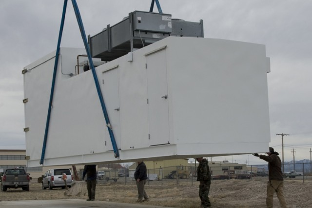 The 15-ton solar radiation test facility is lifted for placement on a prepared concrete pad Feb. 17, 2016 at Dugway Proving Ground. The 8X10-foot chamber is at the higher end, at left. The middle contains equipment to control the lamps, temperature and humidity. The controllers' room is at right. (Photo by Al Vogel, Dugway Public Affairs)