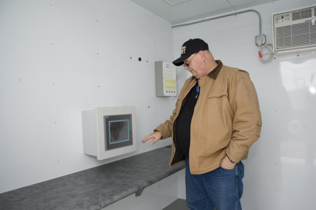 Jim Barnett, chief of the Smoke & Obscurants Branch, looks over the controllers' room, where one person will monitor the replicated sunlight, and another the temperature and humidity, produced in the chamber. Items frequently exposed to the sun, used by Soldiers, will be challenged in the chamber under varying environmental conditions. (Photo by Al Vogel, Dugway Public Affairs)