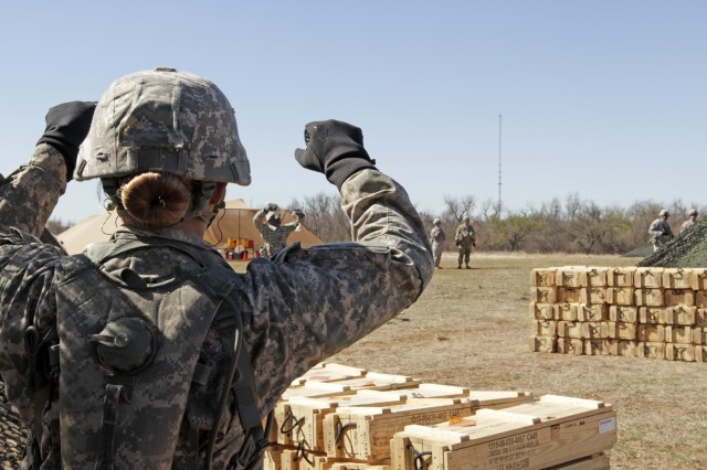 Pfc. Katherine Beatty gives tips to her teammate, who is holding four excess gunpowder bags that weren't needed for the three-increment charge during live-fire training on the M119A3 howitzer, March 1, 2016. Beatty is the Army's first woman 13B cannon crewmember to graduate from advanced individual training, which is taught by 1st Battalion, 78th Field Artillery.