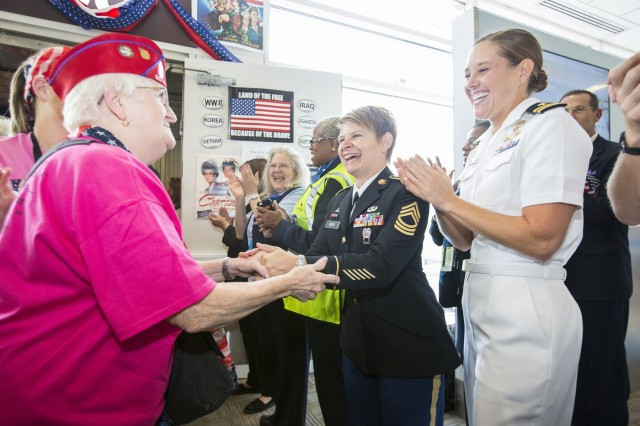 "U.S. Army Master Sgt. Annette Reed, center, shakes the hand of one of 75 female veterans who took part in the first all-female honor flight in the United States Sept. 22, 2015, at Ronald Reagan Washington National Airport in Arlington, Va. The airport's Honor Flight Guardian Coordinator, Laura Robertson, conducted a two-hour Honor Flight Guardian training seminar March 1 at Arlington Public Library. The seminar allowed Robertson to screen potential ""guardians"" (volunteers) who serve as escorts for the hundreds of World War II, Korean War and Vietnam War veterans who visit Washington D.C. as part of the Honor Flight program. Guardians are screened to ensure they are dependable, physically fit and relatable, Robertson said. (Joint Base Myer-Henderson Hall PAO photos by Nell King)"