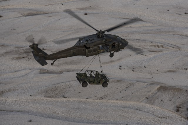 A UH-60L Black Hawk helicopter from 3rd Battalion, 227th Aviation Regiment, 1st Air Cavalry Brigade, Task Force Spearhead, 12th Combat Aviation Brigade, carries a HMWVV across a dry riverbed as part of sling load training with 173rd Airborne Brigade, at Frida drop-zone, Pordenone, Italy, Mar. 9, 2016. Sling load training prepares Soldiers to deliver and move equipment in a quick, safe and efficient manner. (U.S. Army photo by Sgt. Thomas Mort, 12th CAB)
