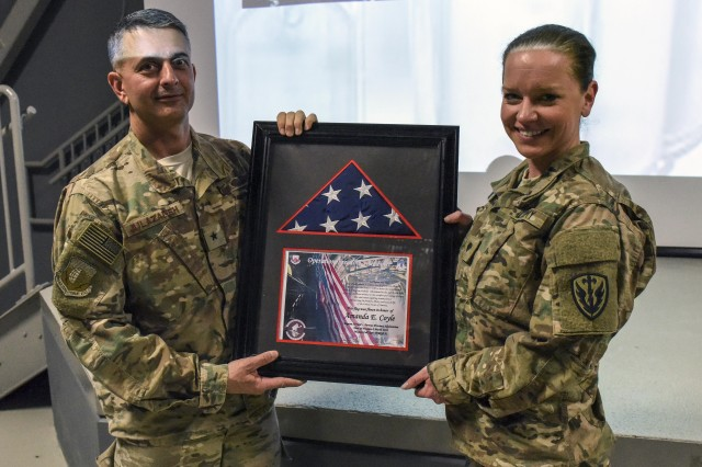 Spc. Amanda Coyle (right), receives a framed flag and certificate from U.S. Air Force Brig. Gen. David Julazadeh, 455th Air Expeditionary Wing commander, following a ceremony, March 7, at Bagram Airfield, Afghanistan.