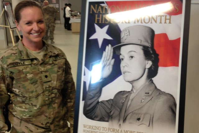 "Spc. Amanda Coyle stands next to a poster highlighting Women's History Month celebrations in Afghanistan. Coyle received recognition from the base commander for her work as a Military Intelligence professional who has conducted 25 patrols ""outside-the-wire"" to collect and analyze intelligence."