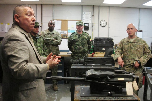Jose Terrones from U.S. Army South translates maintenance procedures into Spanish during a Subject Matter Expert Exchange at the Combined Support Maintenance Shop at McEntire Joint National Guard Base, Eastover, S.C., March 8, 2016. Maintenance officers from the Colombian army toured South Carolina Army National Guard maintenance facilities during a State Partnership Program Subject Matter Expert Exchange held March 7-11, 2016. The Colombian army officers toured facilities in Columbia, Darlington and Charleston, to share best practices and watch Soldiers perform maintenance on a variety of vehicles.