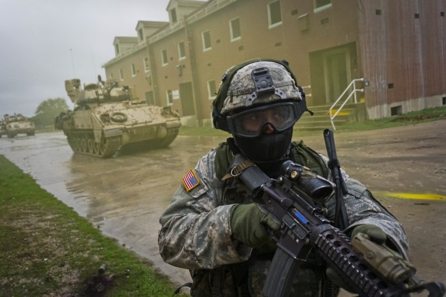 A Soldier with Company B, 2nd Battalion, 7th Cavalry Regiment, 3rd Armored Brigade Combat Team, 1st Cavalry Division, moves through an urban training facility, March 10, at Fort Hood, Texas. The Soldiers used simulation rounds to enhance the realism of training.