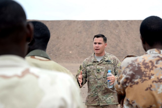 U.S. Army Sgt. Rob Shelton, Regionally Aligned Forces instructor, speaks to members of the Djiboutian Armed Forces, March 10, 2016, before basic rifle marksman training at Arta range in Djibouti. Pairs of FAD soldiers carried a litter 100 meters before even picking up their weapon to increase their heart rate to simulate combat stress.