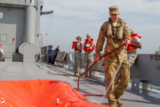 Chief Warrant Officer 2 McKayla Dembowski, a pilot with Company B, 1st Squadron, 104th Cavalry Regiment, 40th Combat Aviation Brigade, sprays off the salt water from the life raft used after a combined search and rescue exercise with the Kuwaiti air force and navy in the Persian Gulf, March 9, 2016. The exercise allowed Kuwaiti military forces to practice recovery techniques during a realistic training mission.