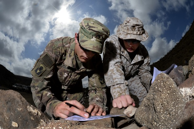 U.S. Army Cpl. Gregory McLellan and U.S. Marine Corps Cpl. Clinton Smith, Joint Corporals Leadership Development Course students, plot grid points during the land navigation portion of Camp Lemonnier's Joint Corporal's Leadership Development Course at Arta, Djibouti, March 3, 2016.