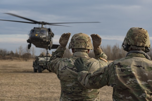 A U.S Army Soldier from 173rd Airborne Brigade signals and directs a UH-60L Black Hawk helicopter from 3rd Battalion, 227th Aviation Regiment, 1st Air Cavalry Brigade, Task Force Spearhead, 12th Combat Aviation Brigade, over a HMWVV, as part of sling load training with 173rd Airborne Brigade, at Frida drop-zone, Pordenone, Italy, Mar. 9, 2016. Sling load training prepares Soldiers to deliver and move equipment in a quick, safe and efficient manner. (U.S. Army photo by Sgt. Thomas Mort, 12th CAB)
