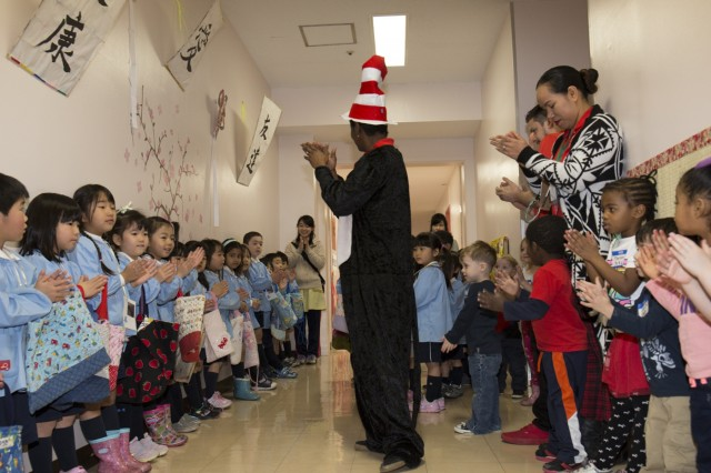 "Audrey Daugherty, facility director for SFHA CDC dressed as Dr. Seuss' Cat in the Hat, leads SFHA CDC children and Hosen Kindergartners in a song, March 11 during visit called ""Unity Day,"" held at the SFHA CDC. (U.S. Army photo by Alia Naffouj)"