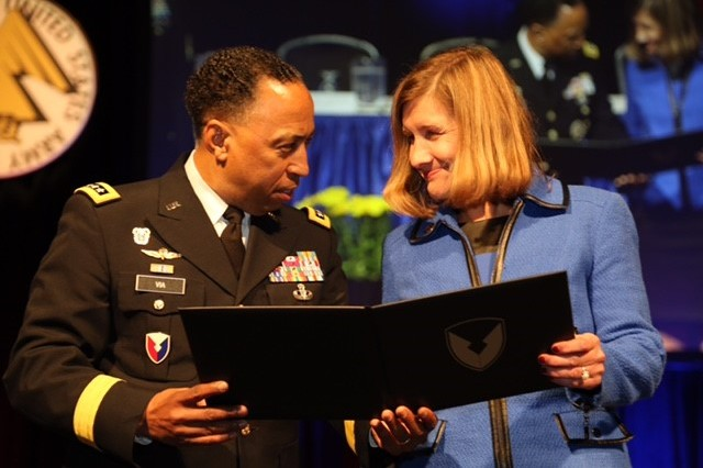 "Gen. Dennis L. Via, Army Materiel Command commander, presents Dr. Susan Myers, the wife of Maj. Gen. Harold Greene, the honorary Maj. Gen. Harold ""Harry"" J. Greene Award for Innovation."