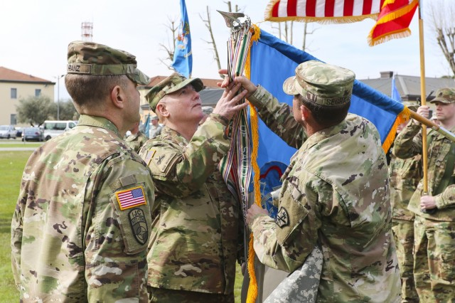 Maj. Gen. George Franz III, commanding general of Intelligence and Security Command, observes as Col. Timothy Higgins, 207th Military Intelligence Brigade commander, and his senior enlisted leader, Command Sgt. Maj. Kenneth Segraves, unfurl the campaign streamers on a new unit guidon during the activation ceremony of 207th MI Bde. March 16, 2016 here at Hoekstra Field at Caserma Ederle. The 207th MI Bde. will serve as the Theater Intelligence Brigade for U.S. Africa Command and is under operational control of U.S. Army Africa. The brigade includes the 207th MI Bde. Headquarters and 307th MI Battalion located here, as well as the 522nd MI Battalion located at Wiesbaden, Germany and the 337th MI Battalion located at Fort Sheridan, Ill. (U.S. Army Africa photo by Staff Sgt. Lance Pounds)