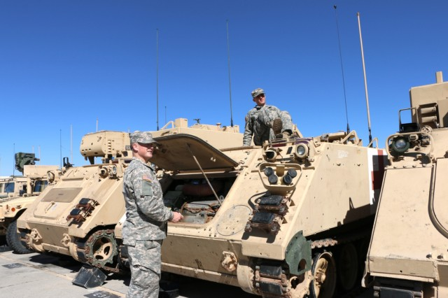 During the Network Integration Evaluation 16.2 Fleet Build, two medic Soldiers inspect their vehicle after arriving at the Integration Motor Pool at Fort Bliss, Texas.