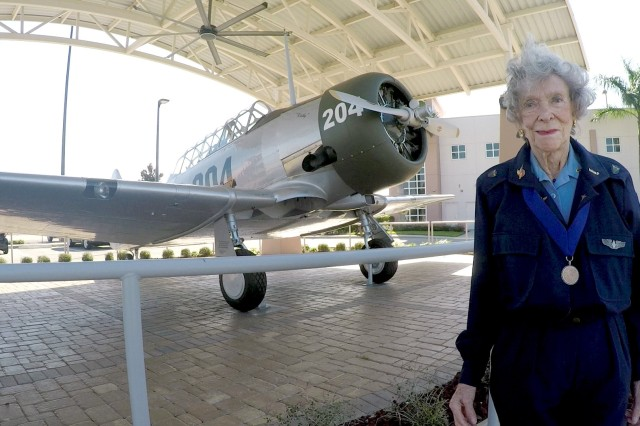Bernice Haydu, a Women Airforce Service Pilot, or WASP, during World War II, stands next to an AT-6 Texan at Page Field near Fort Myers, Florida, Feb. 20, 2016. The WASPs flew Texans during flight training at Avenger Field in Sweetwater, Texas.