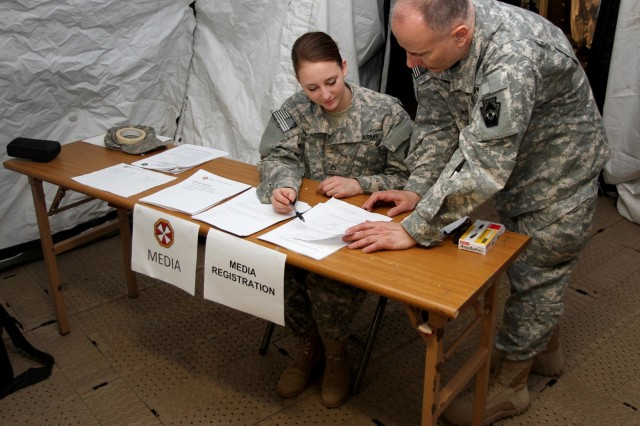Pfc. Hannah Baker and 1st Sgt. Steve Markowski, both members of the Pennsylvania Guard's 109th Mobile Public Affairs Detachment, 213th Regional Support Group, Pennsylvania Army National Guard set up and staffed the media registration desk for a notional press conference during their annual training to South Korea.