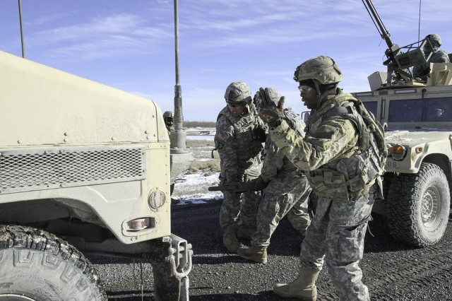 """Soldiers assigned to A Company """"Iron Horse,"""" 210th Brigade Support Battalion, 2nd Brigade Combat Team, execute a scenario-driven convoy live-fire exercise on a closed course that tested their ability to react to small-arms fire, request medical evacuation, react to improvised explosive devices and conduct vehicle recovery operations, while they provided overwatch security."""
