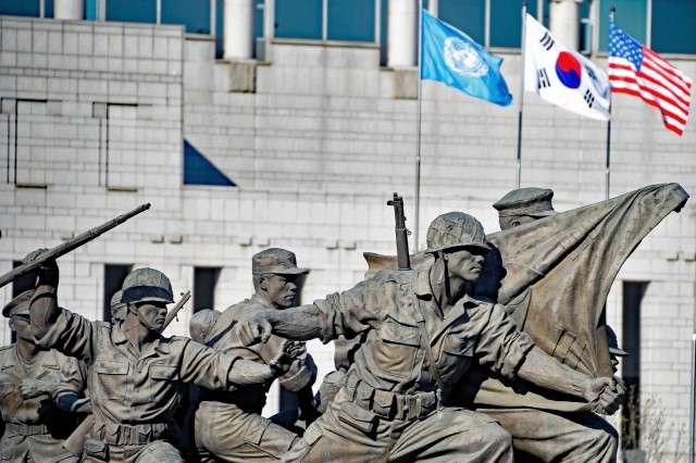 The United Nations, Republic of Korea and U.S. flags fly in the background of a statue depicting Soldiers fending off a North Korean attack during the Korean War outside the War Memorial of Korea in Seoul. Patrons visiting the museum are treated to a variety of outdoor exhibits that were established in 2003 to mark the 50-year anniversary of the signing of the 1953 Armistice that brought hostilities of the war to an end. (Photo by Tim Oberle, Eighth Army Public Affairs)