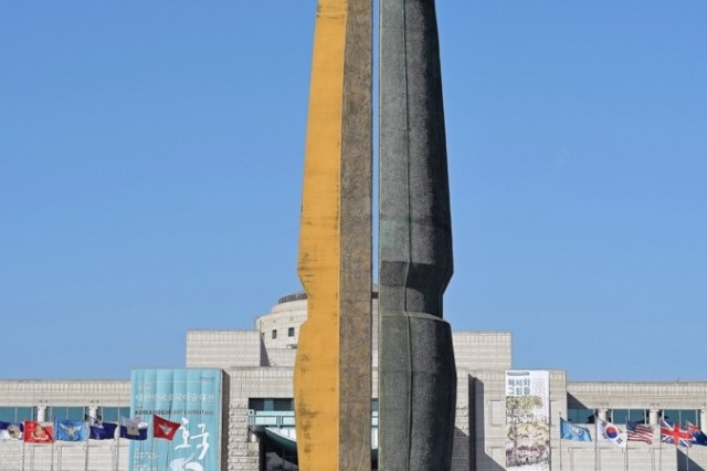 "An art sculpture entitled the ""Hoguk Gunsang"" towers outside the War Memorial of Korea as performers put on a traditional Korean performance in the Fall of 2015. Performances are common place outside the museum, and beginning in April the Republic of Korea Honor Guard will perform every Friday for the general public. (Photo by Tim Oberle, Eighth Army Public Affairs)"