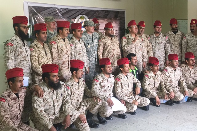 U.S. Soldiers Lt. Col. Jason Czar (center), Office of the Program Manager-Saudi Arabian National Guard senior security advisor, and Maj.  Daniel Campbell (at left), an OPM-SANG military schools advisor, pose for a photo with members of Saudi Arabia's G3 Military Police Command and instructors of Riyadh's Military Police Training Academy after graduation ceremonies in Saudi Arabia March 3.  The OPM-SANG mission is to manage the Modernization Program of the Saudi Arabian National Guard under the terms of a memoranda of understanding between the U.S. Government and the Saudi Arabian government. To do this, OPM-SANG uses military and civilian teams assigned to Saudi Arabia to provide advice and assistance in the modernization, encompassing training, equipment, maintenance, supply, procurement, management, organization, health care and facilities.OPM-SANG is a subordinate command of the U.S. Army Security Assistance Command.