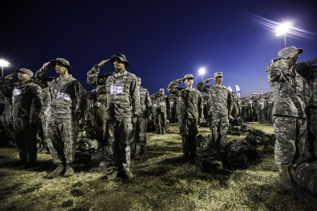Service members salute the flag during the playing of the national anthem right before the kickoff of the White Sands Missile Range's 27th annual Bataan Memorial Death March.