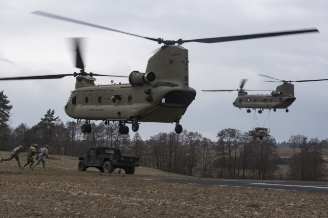 "Soldiers from the 44th Expeditionary Signal Battalion, 2nd Signal Brigade rush to hook up a HWMMV to a a CH-47 Chinook Helicopter from Hotel Company, 1st Battalion, 214th Aviation Regiment, 12th Combat Aviation Brigade, ""Big Windy"", as part of sling load and air operations training, March 22, 2016 at the Grafenwoehr Training Area, Germany. (U.S. Army photo by Sgt. Thomas Mort, 12th CAB)"