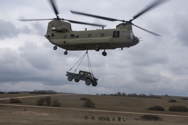 "A CH-47 Chinook Helicopter from Hotel Company, 1st Battalion, 214th Aviation Regiment, 12th Combat Aviation Brigade, ""Big Windy"", hauls a HWMMV to its destination after being sling loaded by Soldiers from the 44th Expeditionary Signal Battalion, 2nd Signal Brigade, as part of sling load and air operations training, March 23, 2016 at the Grafenwoehr Training Area, Germany. (U.S. Army photo by Sgt. Thomas Mort, 12th CAB)"