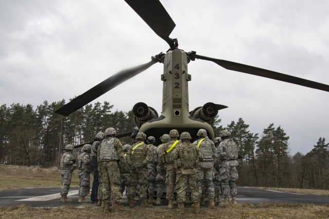 "Soldiers from the 44th Expeditionary Signal Battalion, 2nd Signal Brigade gather for instructions from a CH-47 crew chief from Hotel Company, 1st Battalion, 214th Aviation Regiment, 12th Combat Aviation Brigade, ""Big Windy"", in preparation for sling load and air operations training, March 23, 2016 at the Grafenwoehr Training Area, Germany. (U.S. Army photo by Sgt. Thomas Mort, 12th CAB)"