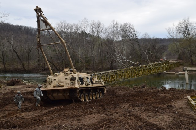 Engineers from the 595th Engineer Company maneuver a M88 Recovery Vehicle into position to begin dragging the 90,000-pound aluminum bridge that was blocking boat traffic on the Big Piney River. Flood waters knocked the bridge into the river.