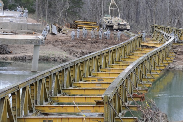 Engineers from the 595th Engineer Company assess progress in the early stages of dragging the bridge of out the Big Piney River.