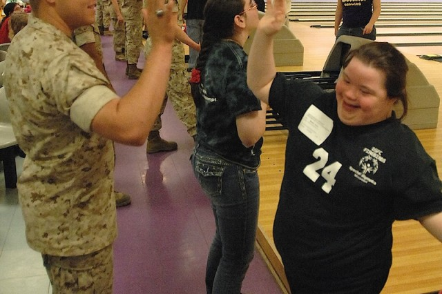 Dana Marler, from the Franklin County School District in New Haven, Mo., is all smiles as she gets a high-five from Marine Pfc. Alex Hill after bowling a strike during the 2016 SOMO State Indoor Games at Daugherty Bowling Center. It was Marler's second strike of the opening game of the tournament.