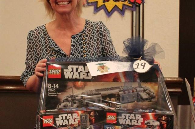 Community member, Christi Bosetti, wins the Star Wars basket at the ZaCSA Auction: Heroes vs. Villains, held March 19 at the Camp Zama Community Club. (U.S. Army photo by Tara Ladd)