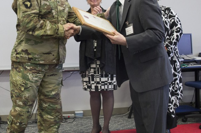 Col. William B. Johnson, commander of U.S. Army Garrison Japan, presents Benjamin Kolodziej, gifted education teacher at Arnn, with the award for District Teacher of the Year from U.S. DoDEA Japan District March 21 in Arnn's information center. (U.S. Army photo by Lance D. Davis)