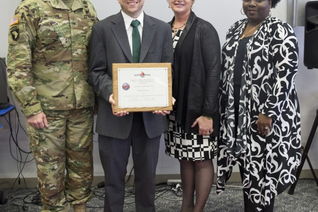 """Benjamin Kolodziej, gifted education teacher, was named """"District Teacher of the Year"""" for 2016-2017 by U.S. DoDEA Japan District March 21 at Arnn Elementary on the Sagamihara Family Housing Area installation. Col. William B. Johnson, commander of U.S. Army Garrison Japan, along with Lois Rapp, superintendent of DoDEA-Pacific Japan District, and Gwendolyn Baxter-Oakley, principal of Arnn, pose for a picture after presenting Kolodziej an award. (U.S. Army photo by Lance D. Davis)"""