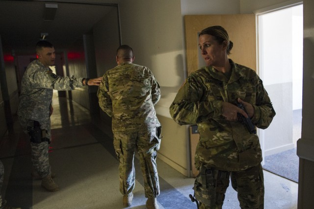 U.S. Army Reserve Sgt. Maj. Nita Harvey, operations sergeant major for the 607th Military Police Battalion, of the 200th MP Command, stands at the low-ready providing rear security for her team in a hallway clearing drill during a two-day joint training exercise conducted by the Grand Prairie Police Department in Mansfield, Texas, March 24. More than 15 service members, including Marines from the same Reserve Center, partnered to share and learn police tactics and techniques. (U.S. Army photo by Staff Sgt. Shejal Pulivarti)