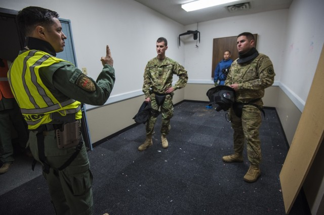 A police officer from the Grand Prairie Police Department provides instruction to U.S. Army Reserve Soldiers from the 607th Military Police Battalion, of the 200th MP Command, during a simulated round drill that tested skills learned during a two-day joint training exercise conducted by the GPPD in Mansfield, Texas, March 24. More than 15 service members, including Marines from the same Reserve Center, partnered to share and learn police tactics and techniques. (U.S. Army photo by Staff Sgt. Shejal Pulivarti)