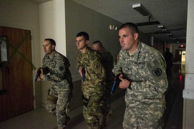 U.S. Army Reserve Sgt. Kevin Moore (left), Spc. Austin Dunaway, and Sgt. Clinton Condo, all military police from the 607th Military Police Battalion, of the 200th MP Command, prepare to clear a hallway during a two-day joint training exercise conducted by the Grand Prairie Police Department in Mansfield, Texas, March 24. More than 15 service members, including Marines from the same Reserve Center, partnered to share and learn police tactics and techniques. (U.S. Army photo by Staff Sgt. Shejal Pulivarti)