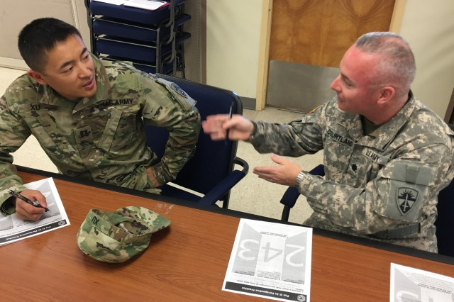 """Capt. Li Xu (left), commander of HHC, U.S. Army Operational Test Command, discusses a shared everyday experience with Lt. Col. Christopher Courtland, an operational test officer with OTC's maneuver test directorate, during an evolution of Master Resiliency Training called """"Put It In Perspective,"""" which focuses Soldier attention on the deciding factors needed to prevent matters from automatically going into the worst-case scenario."""