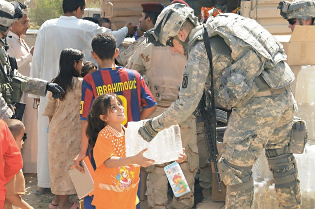 Cpl. John M. Laursen helps to distribute water and food to Iraqi citizens in June 2010 in Baghdad, Iraq.