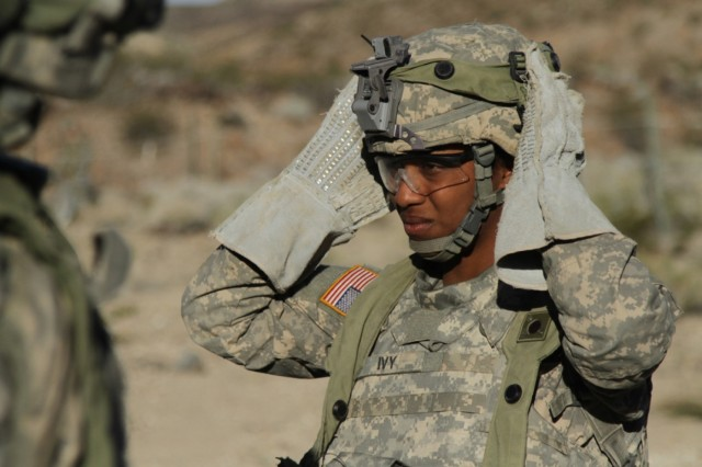 """Pvt. Lashonda Ivy, a combat engineer with 43rd Combat Engineer Company, Regimental Engineer Squadron """"Pioneer,"""" 3rd Cavalry Regiment, dons her helmet during training at the National Training center in Fort Irwin, California earlier this year. (Photo by Spc. Josephine Carlson, 982 Combat Camera Company, Airborne)"""