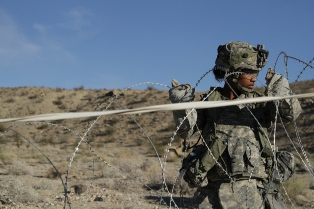 U.S. Army Pvt. Lashonda Ivy,  assigned to 43rd Combat Engineer Co., Regimental Engineer Squadron, 3d Cavalry Regiment, place concertina wire as part of a defense at the National Training Center in Fort Irwin, Calif, Feb. 13, 2016. While at NTC, Soldiers undergo tough, realistic Unified Land Operations with other participants to prepare Brigade Combat Teams and other units for combat. (U.S. Army photo by Spc. Josephine Carlson/Released.)
