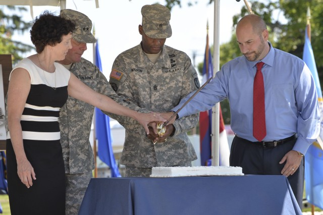 Kathy Heikel, Maj. Gen. Mark McDonald, commanding general of the U.S. Army Security Assistance Command, Command Sgt. Maj. Dana S. Mason, Jr., USASAC's command sergeant major, and Christopher Grabowicz cut the ceremonial cake during the 50th anniversary celebration of USASAC held July 23, 2015 on New Cumberland's parade field. Heikel and Grabowicz represented USASAC New Cumberland's longest serving and newest employees, respectively.