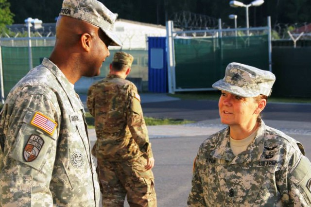 Command Sgt. Maj. Sheryl Lyon of U.S. Army Europe talks with then-commandant of the NCO Academy in Grafenwoehr, Germany, Command Sgt. Maj. Wardell Jefferson, during her visit to observe troops training.