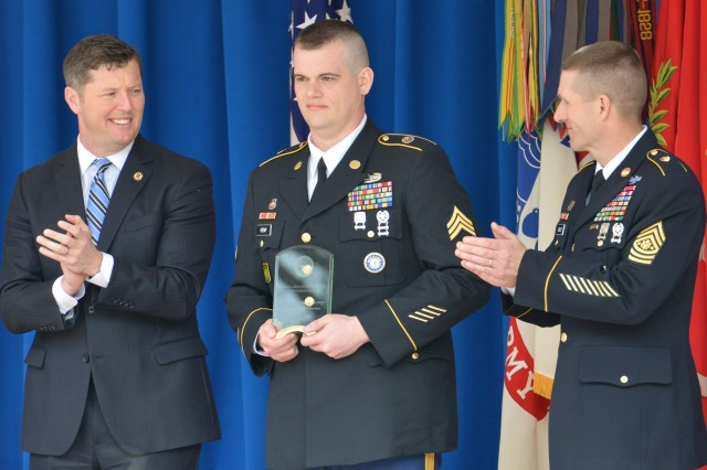 Sgt. Joshua James Kemp (center) of the 2/75th Recruiting and Retention Battalion, Kentucky Army National Guard, displays the Sexual Assault Prevention Innovation Award presented by Acting Secretary of the Army Patrick Murphy (left) as Sgt. Maj. of the Army Daniel Dailey applauds, March 31, 2016.