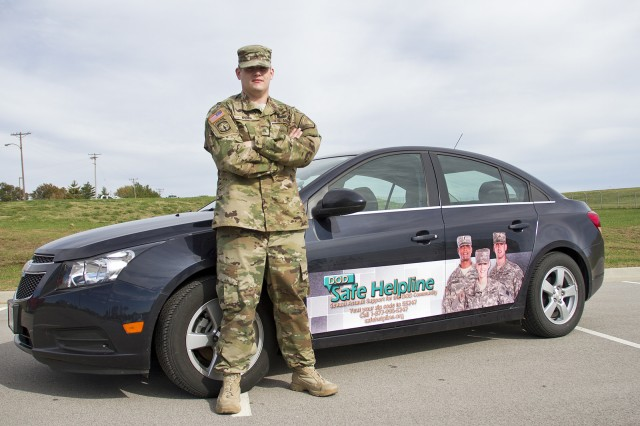 Sgt. Joshua James Kemp of the 2/75th Recruiting and Retention Battalion, Kentucky Army National Guard, stands beside a vehicle displaying the Helpline design that earned him the Sexual Assault Prevention Innovation Award.
