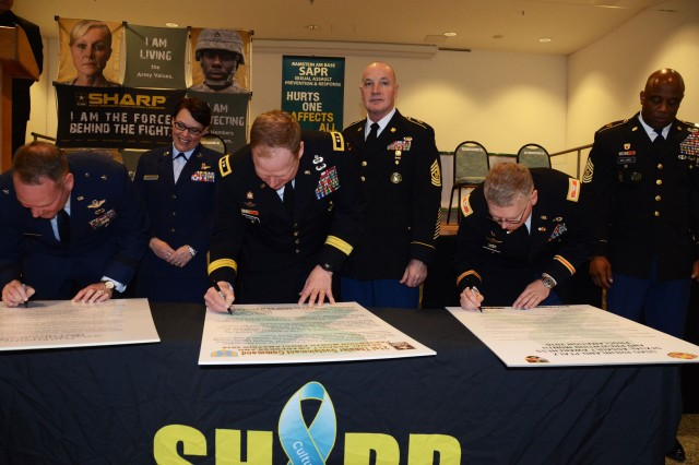 From left, the commanders of the 86th Airlift Wing, 21st Theater Sustainment Command and USAG Rheinland-Pfalz sign their organizations' proclamations to observe April as Sexual Assault Awareness and Prevention Month at the April 1 kick-off ceremony, while their respective senior enlisted leaders look on.