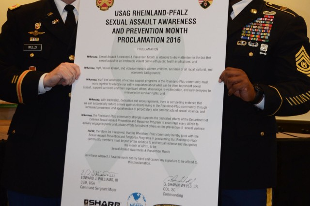 USAG Rheinland-Pfalz Commander Col. G. Shawn Wells Jr., and Command Sergeant Major Edward J. Williams III, hold up the signed proclamation for the garrison declaring the observance of April as Sexual Assault Awareness and Prevention Month.