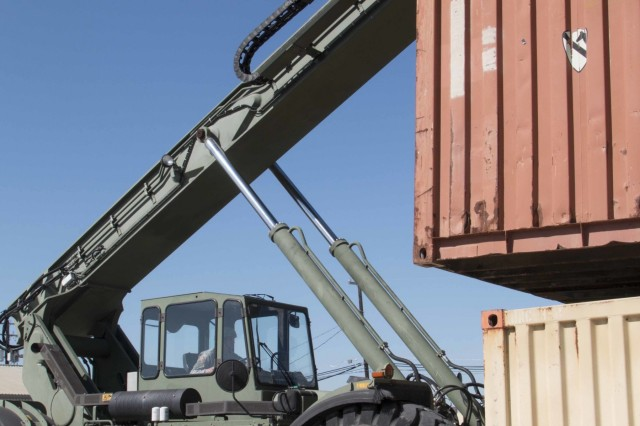 "Spc. Robert Hilyard, a Winterhaven, Florida, native and cargo specialist assigned to the 297th Inland Cargo Transfer Company, 13th Expeditionary Sustainment Command, transfers shipping containers trucks to be taken to the Logistics Readiness Center at Fort Hood Texas, March 22. The container belongs to the 3rd Armored Brigade Combat Team ""Greywolf,"" 1st Cavalry Division, which is spearheading an Army-wide effort to do away with excess, obsolete and unserviceable equipment. This effort will establish the process that the rest of the Army will use to turn-in or laterally transfer equipment"