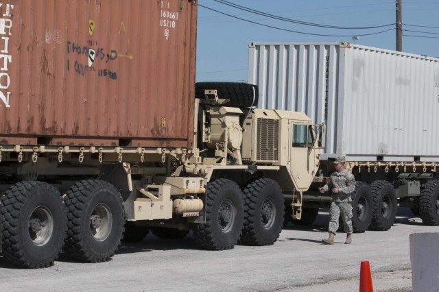 "A Soldier with the 3rd Armored Brigade Combat Team ""Greywolf,"" 1st Cavalry Division ground guides a truck hauling shipping containers out of the III Corps motor pool. The trucks are bound for the Logistics Readiness Center on Fort Hood, Texas.  The Greywolf Brigade is spearheading an Army-wide effort to do away with excess, obsolete and unserviceable equipment. This effort will establish the process that the rest of the Army will use to turn-in or laterally transfer equipment"
